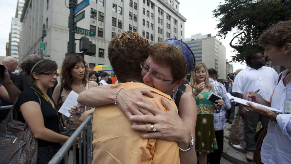 A couple embrace as they line up to be married outside the Manhattan Marriage Bureau in New York on July 24, 2011 . Photo by