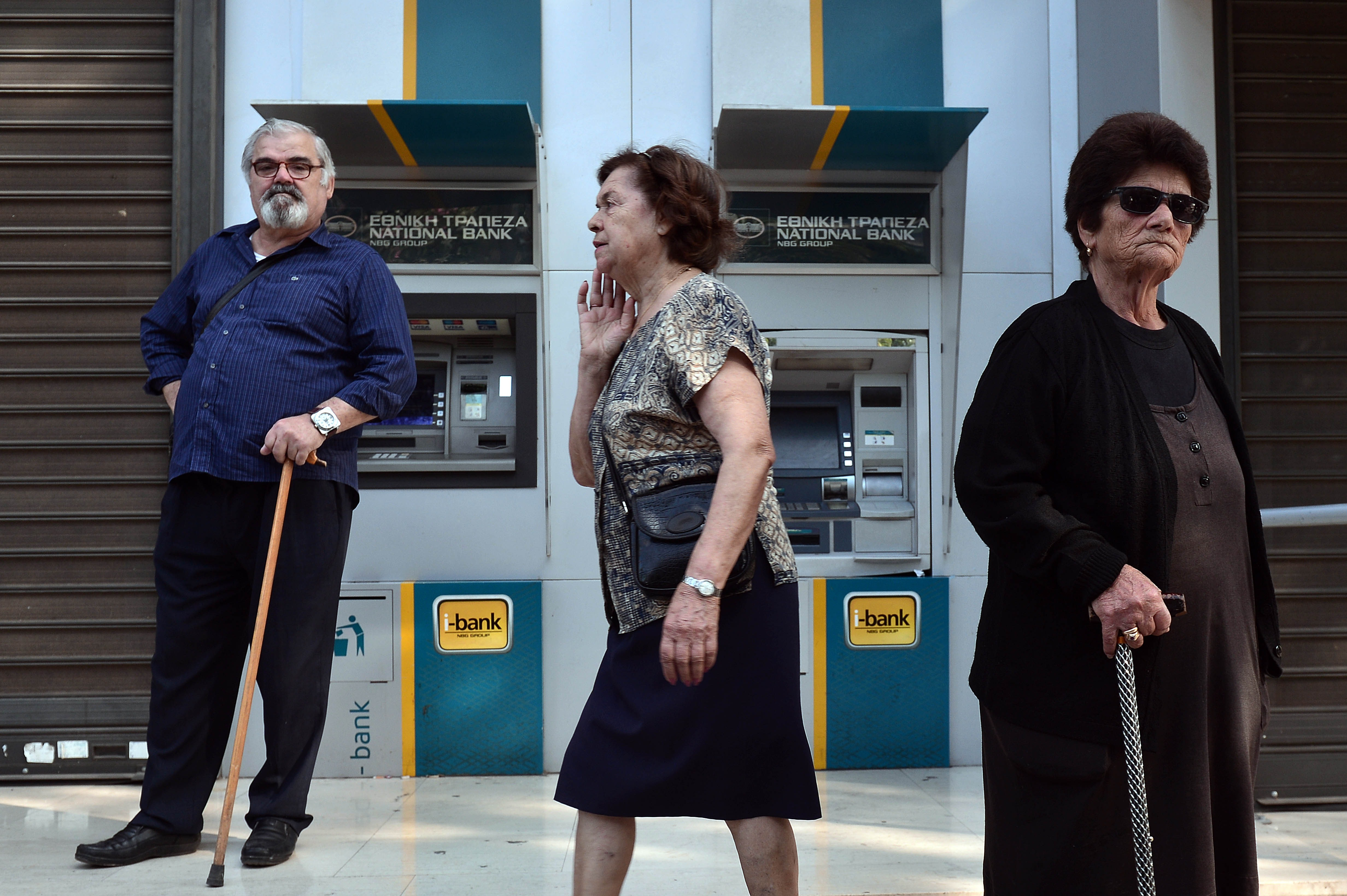 People stand by Greece national bank's empty ATM's in central Athens on June 29, 2015 as Greece ordered its banks to shut for