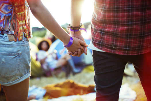 Close up of couple holding hands outside tents at music festival
