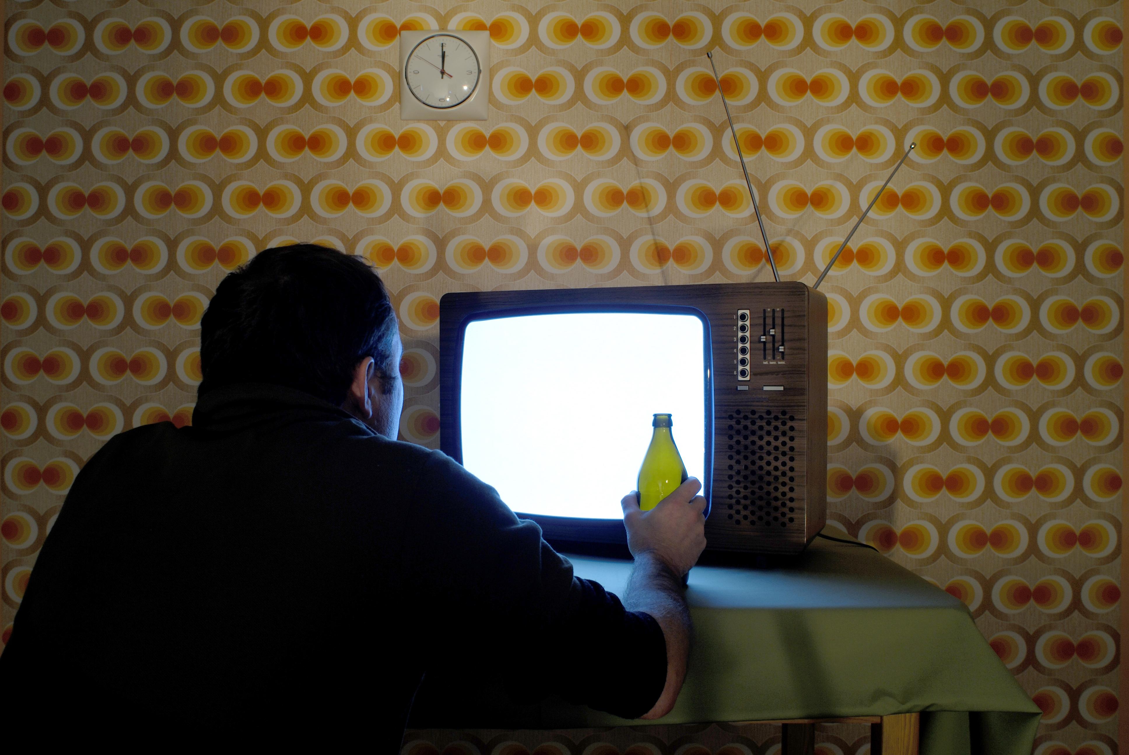 Szene alter Fernseher mit Bierflasche un Person