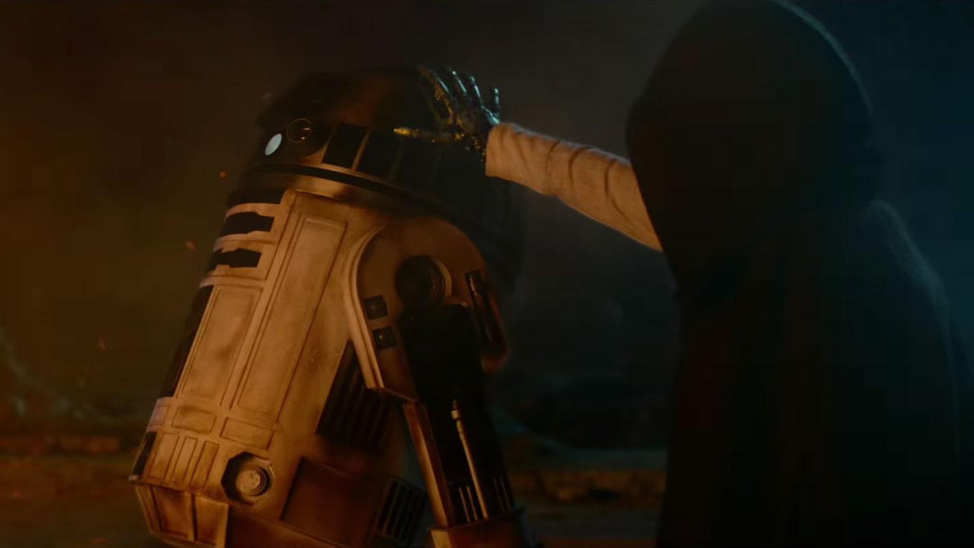 Es wird gemunkelt, dass wir hier Luke Skywalker sehen, der seine Hand auf R2-D2 legt.
