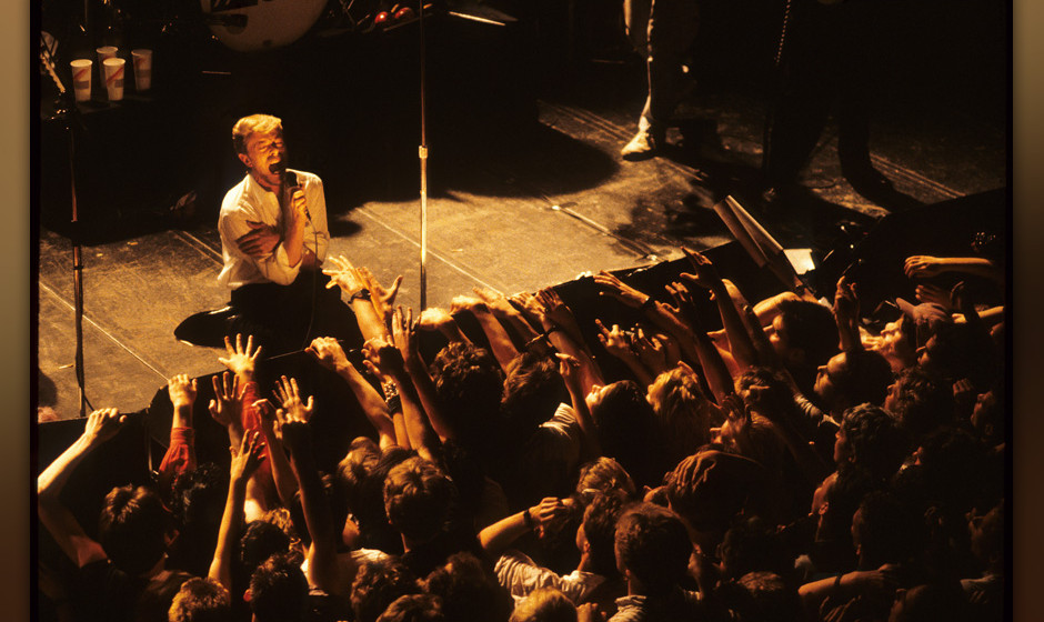 Members of the audience reach up to David Bowie as he kneels at the front of the stage while performing with Tin Machine at P