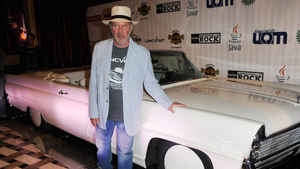 HOLLYWOOD, FL - SEPTEMBER 23: Neil Young poses with a 1959 Lincoln Continental convertible as he appears in support of his Re