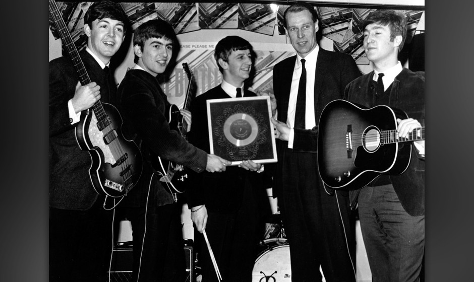 LONDON - 1964: Rock and roll band 'The Beatles' poses for a portrait with their producer George Martin. (L-R) Paul McCartney,