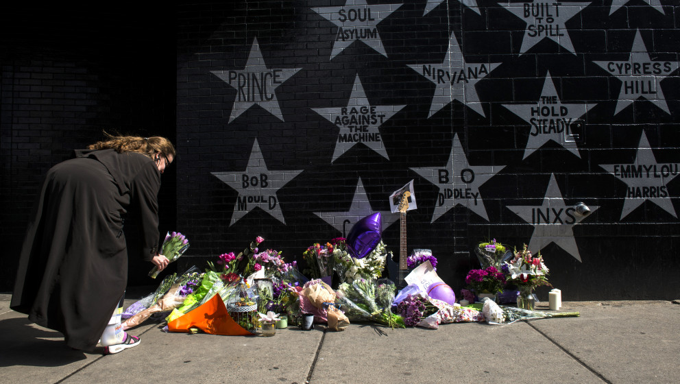 MINNEAPOLIS, MN - APRIL 21: A woman lays flowers at a memorial for Prince outside First Avenue nightclub on April 21, 2016 in