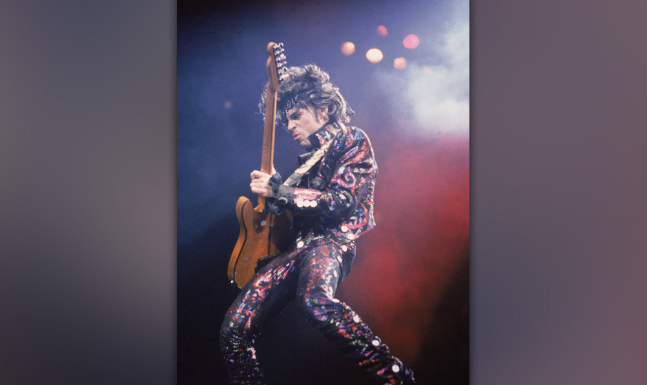 American rock singer and songwriter Prince plays guitar on stage during a concert, 1985. (Photo by Frank Micelotta/Getty Imag