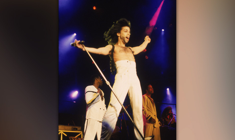 American singer and songwriter Prince stands on stage with his arms outstretched, wearing high-waisted white pants, circa 199
