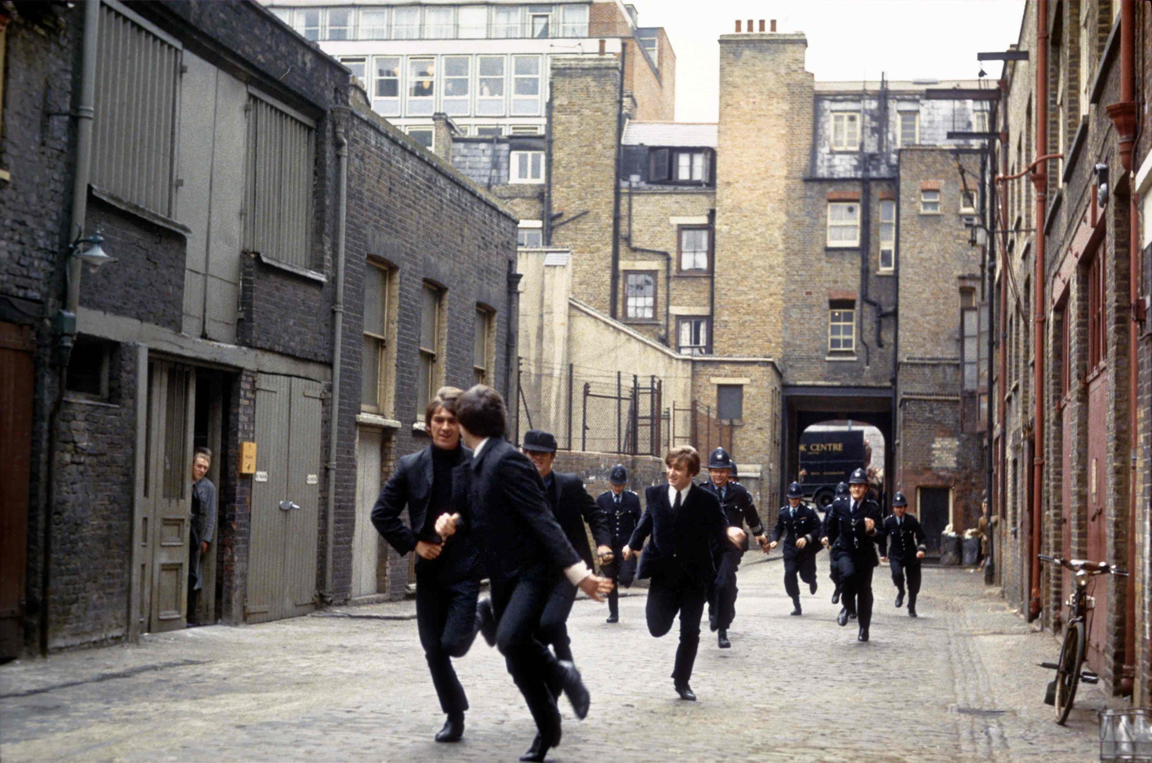 LONDON - 1964: Rock and roll band 'The Beatles' run from the police in a still from their movie 'A Hard Day's Night' which wa