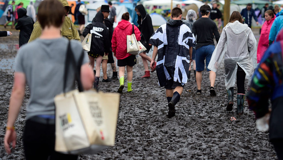 SCHEESSEL, GERMANY - JUNE 24: Visitors wearing plastic rain jackets walk through mud at the camping site of the Hurricane fes