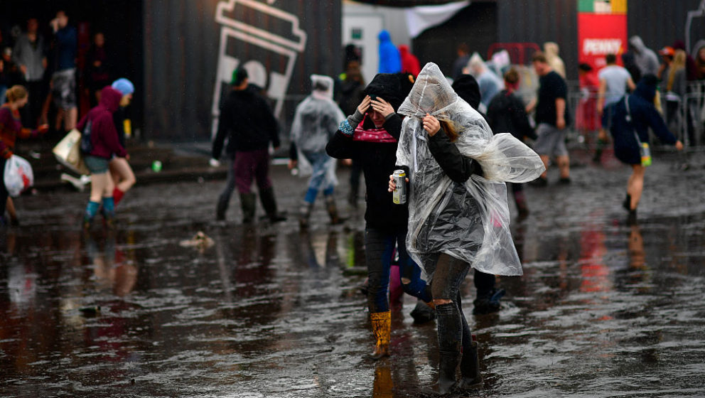SCHEESSEL, GERMANY - JUNE 25: Two girls hide from the rain while walking the muddy camping compound at the Hurricane Festival