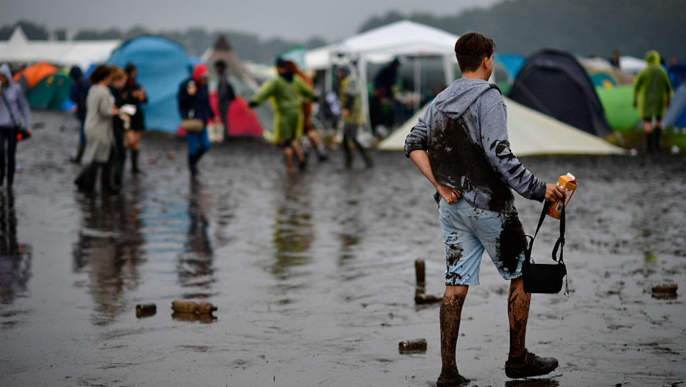 SCHEESSEL, GERMANY - JUNE 25: A male visitor walks the muddy and almost flooded camping compound at the Hurricane Festival co