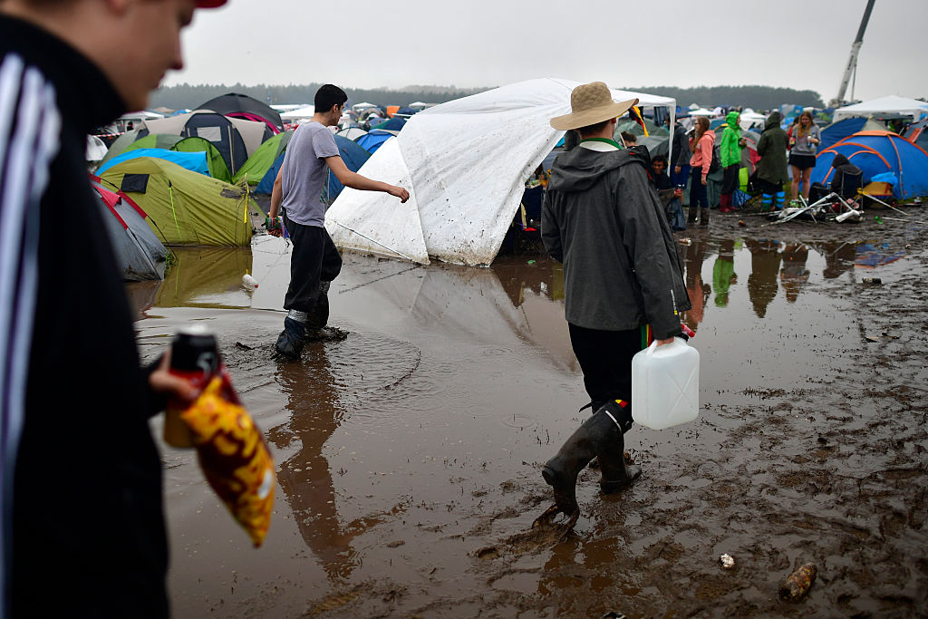 SCHEESSEL, GERMANY - JUNE 25: Three male visitors walk through a puddle at the camping compound at the Hurricane Festival com