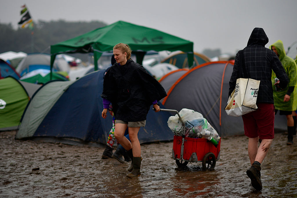SCHEESSEL, GERMANY - JUNE 25: A girl walks on the muddy camping compound at the Hurricane Festival compound on June 25, 2016
