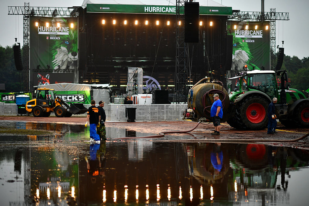 SCHEESSEL, GERMANY - JUNE 25: Service personal stand in a puddle in front of the Green Stage at the Hurricane Festival compou