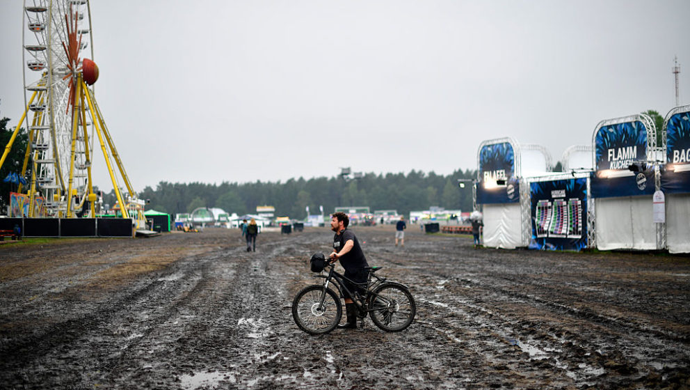 SCHEESSEL, GERMANY - JUNE 25: A service crew member pushes his bike over a muddy field at the Hurricane Festival compound on