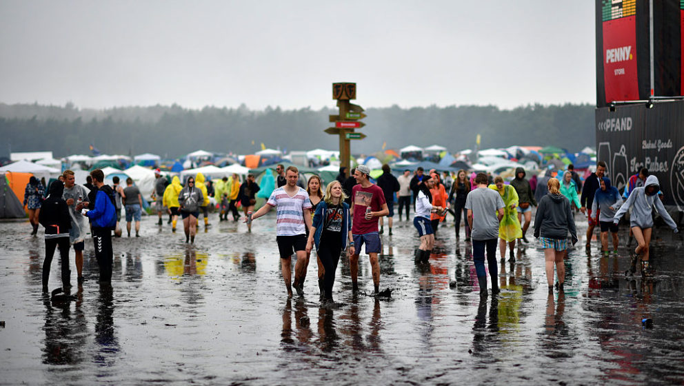 SCHEESSEL, GERMANY - JUNE 25: Visitors walk the muddy camping compound at the Hurricane Festival compound on June 25, 2016 in
