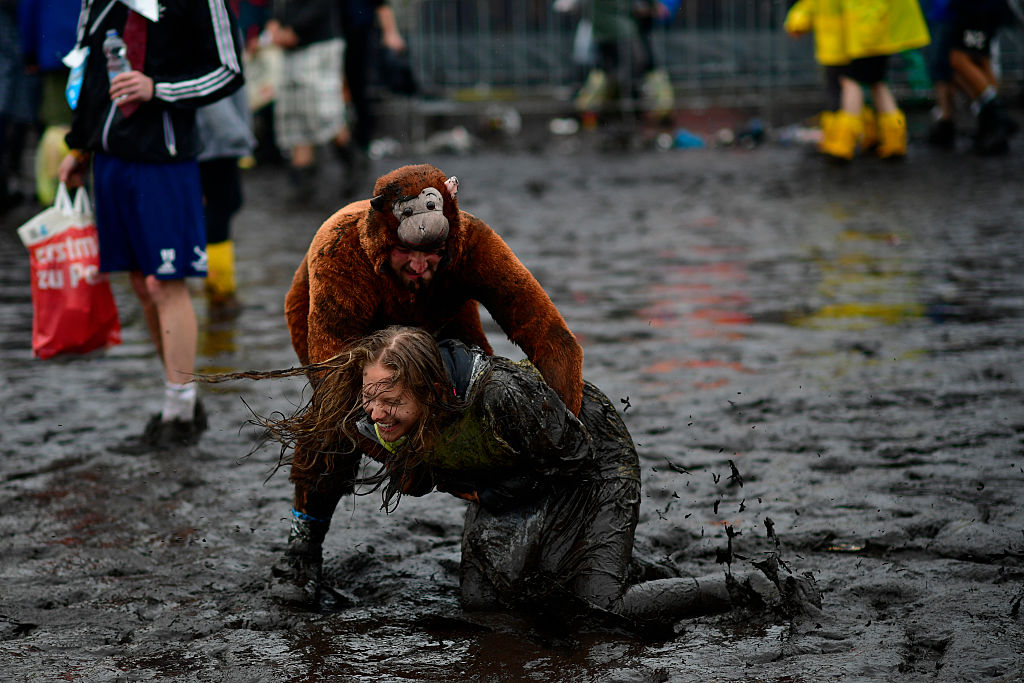 SCHEESSEL, GERMANY - JUNE 25: A male visitors dressed as a monkey plays with a female visitor in the mud at the muddy and flo