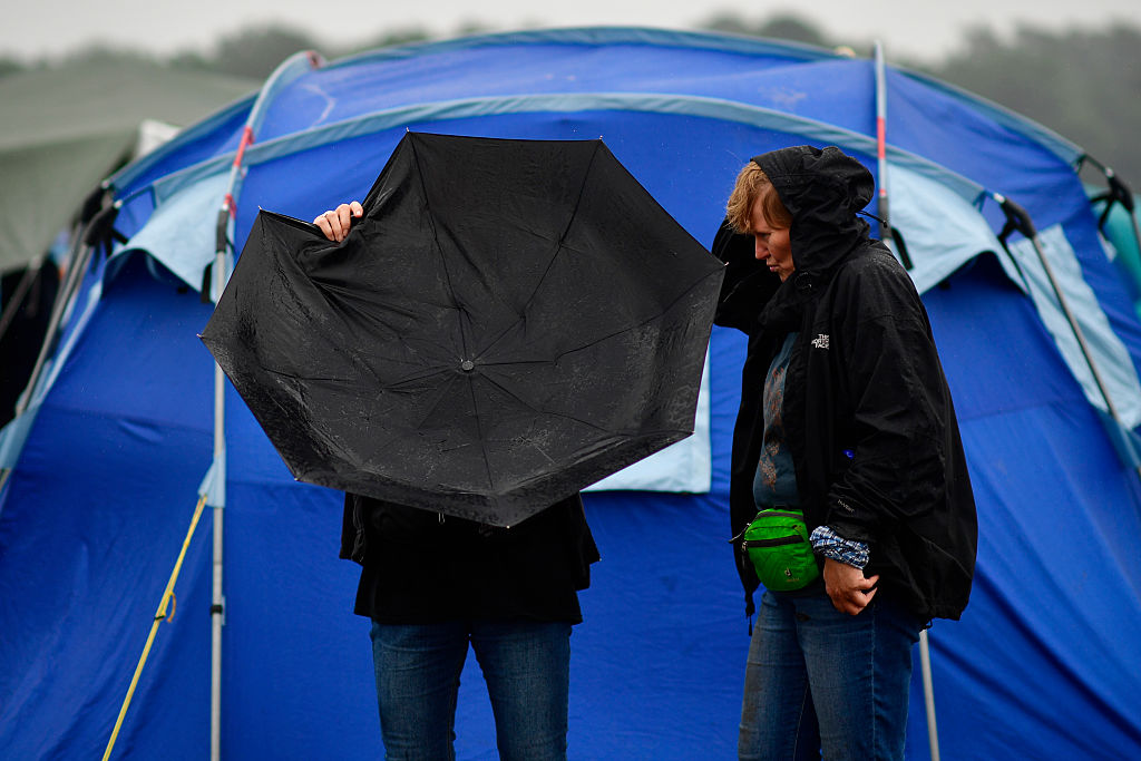 SCHEESSEL, GERMANY - JUNE 25: Two visitors check their umbrella during heavy rain at the muddy camping compound at the Hurric