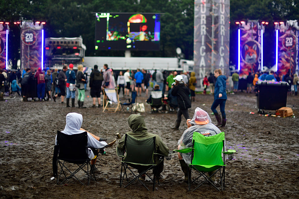 SCHEESSEL, GERMANY - JUNE 25: Three male visitors sit on chair at the muddy camping compound at the Hurricane Festival compou