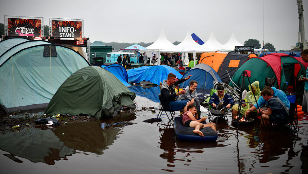 SCHEESSEL, GERMANY - JUNE 25: Visitors have fun while sitting and one lies on an inflatable mattress at the flooded camping c
