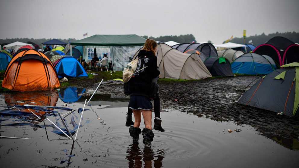 SCHEESSEL, GERMANY - JUNE 25: A girl gives another girl a piggyback ride through a puddle at the flooded camping compound at