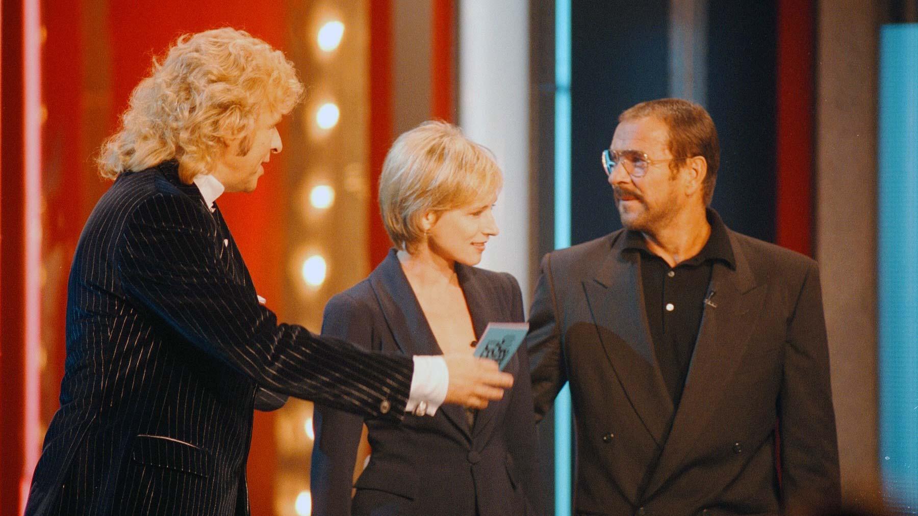 """Thomas Gottschalk mit Corinna Harfouch und Götz George in der """"Wetten, dass.. ?""""-Sendung vom 10.10.1998"""