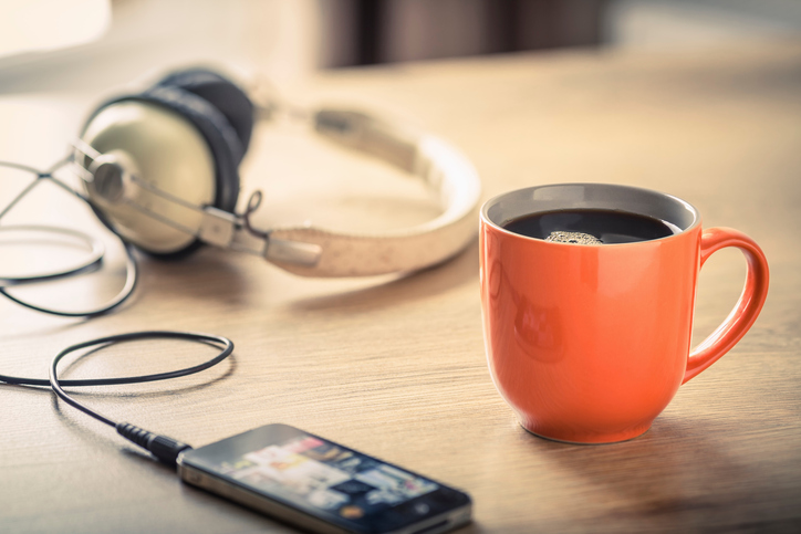 Still life of black coffee, headphones and smartphone