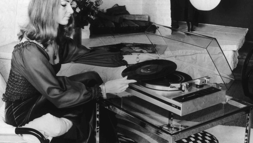 A woman using an automatic record player made by Philips, at the International Radio Show in Berlin, circa 1974. The turntabl