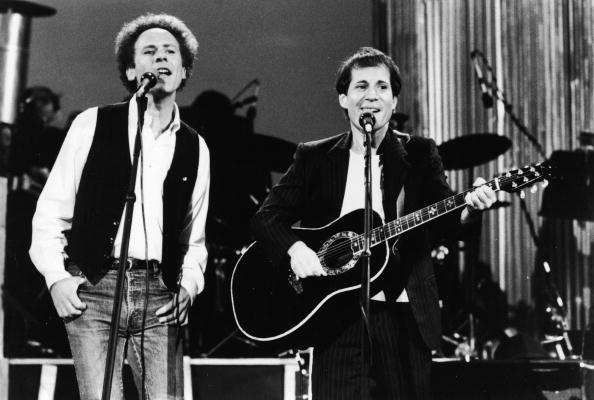 American pop vocal duo Paul Simon (R) and Art Garfunkel perform on stage for a reunion concert at Central Park's Great Lawn,