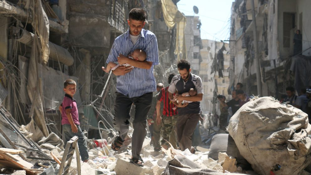 TOPSHOT - Syrian men carrying babies make their way through the rubble of destroyed buildings following a reported air strike