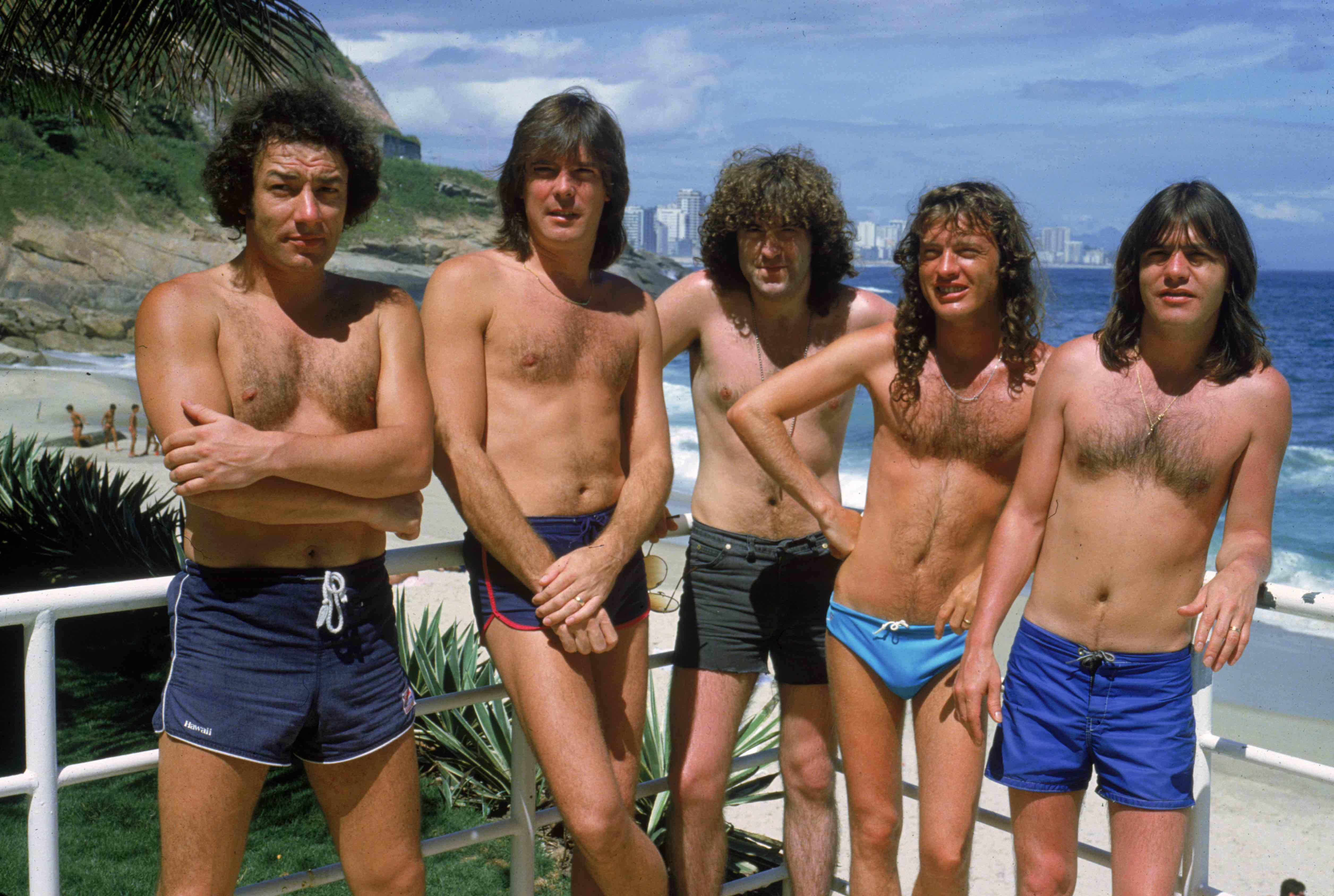 Hard rock group AC/DC at the beach in Ipanema, Brazil during a South American tour, January 1985. Left to right: Brian Johnso