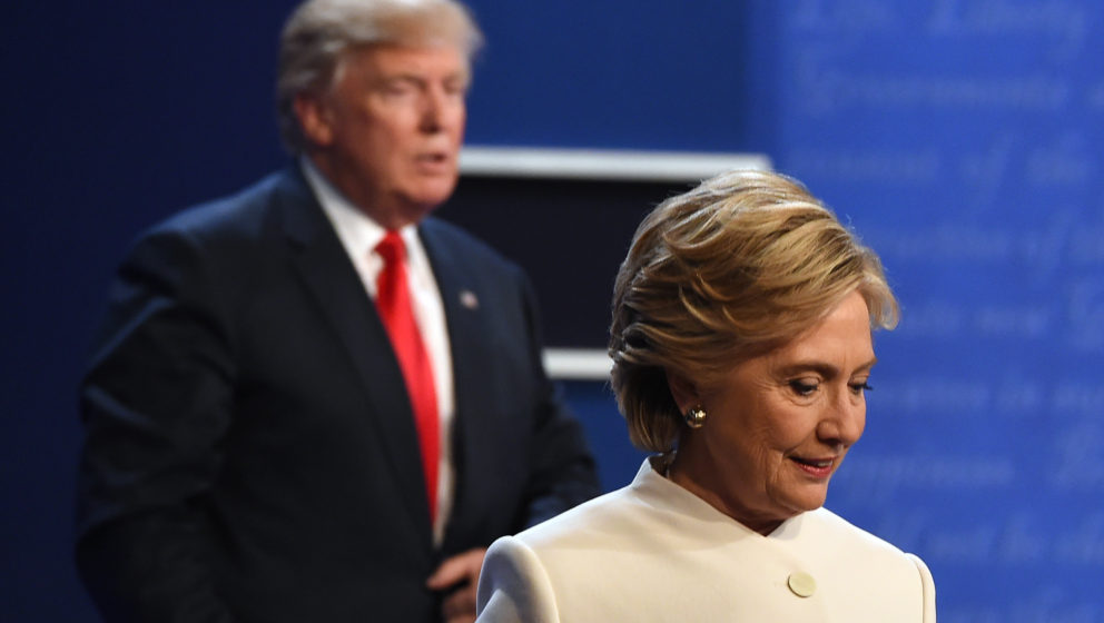TOPSHOT - Democratic nominee Hillary Clinton (R) and Republican nominee Donald Trump walk off the stage after the final presi