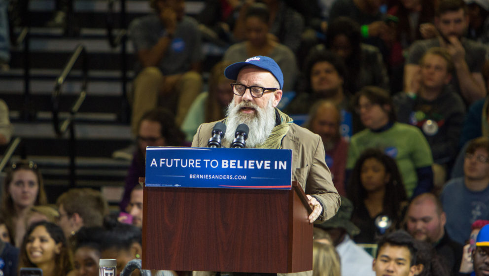 POUGHKEEPSIE, NEW YORK - APRIL 12: Michael Stipe speaks at Senator Bernie Sanders rally at McCann Arena at Marist College on
