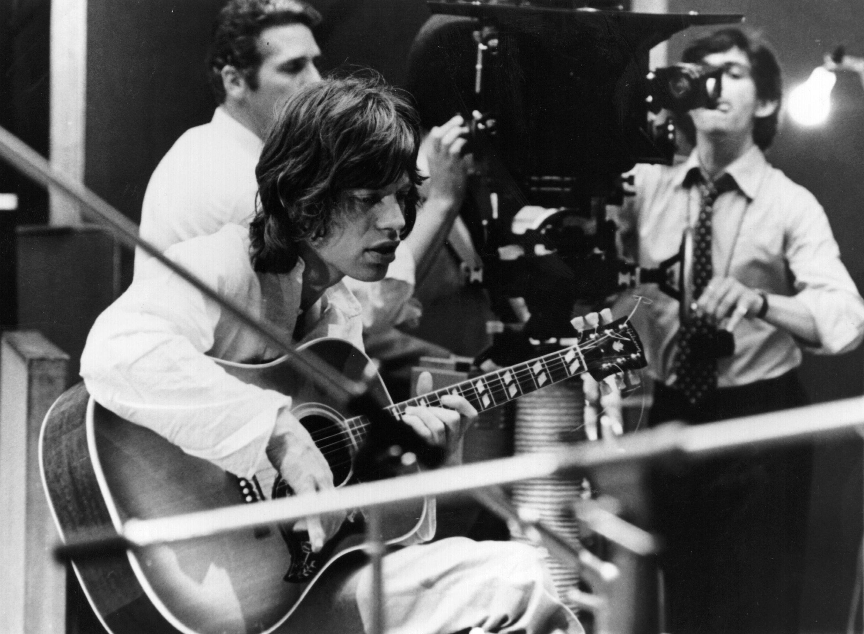 30th July 1968:  Mick Jagger, singer of British rock band the Rolling Stones plays an acoustic guitar in a recording studio d
