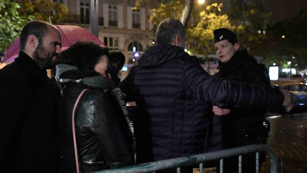 A police officer searches people outside the Bataclan concert hall in Paris on November 12, 2016, prior to the reopening conc