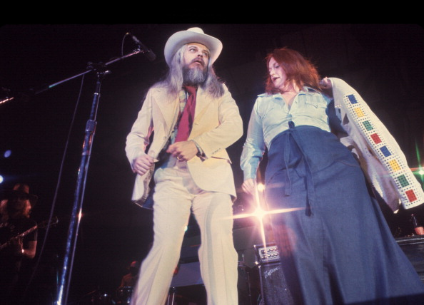 NEW YORK - MAY 1976:  Leon Russell (L.) with woman on stage in performance at Nassau Coliseum, NY May 14, 1976.  (Photo by Wa