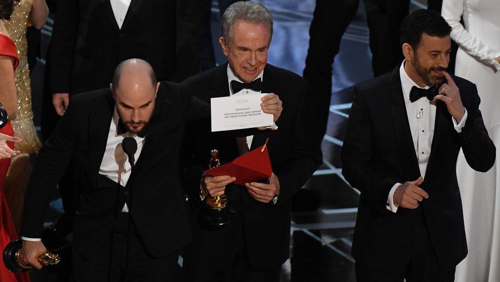 Warren Beatty lächelt und zeigt die Karte, auf der 'Moonlight' steht. Jimmy Kimmel schaut bedröppelt.
