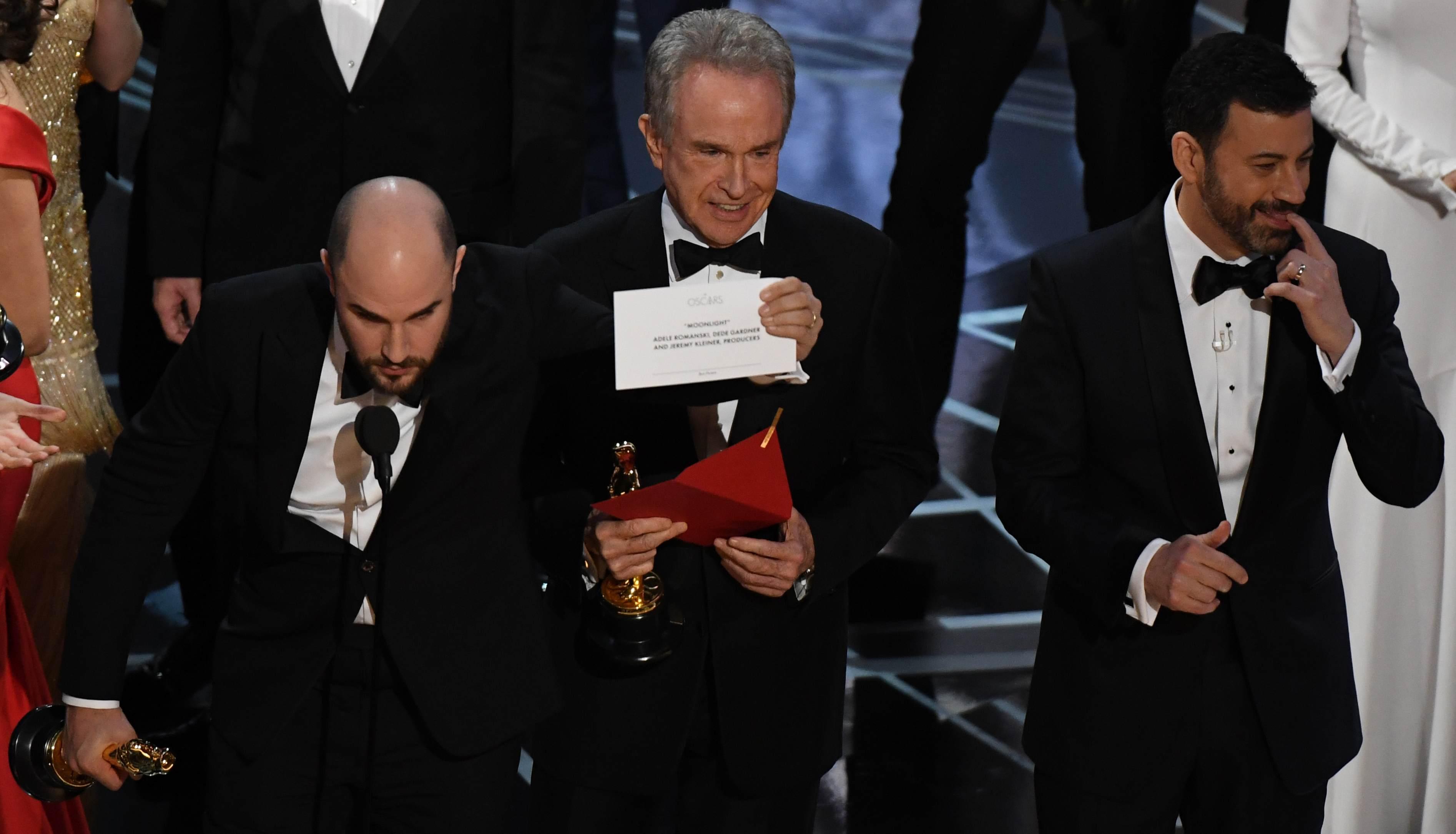 """Warren Beatty lächelt und zeigt die Karte, auf der """"Moonlight"""" steht. Jimmy Kimmel schaut bedröppelt."""