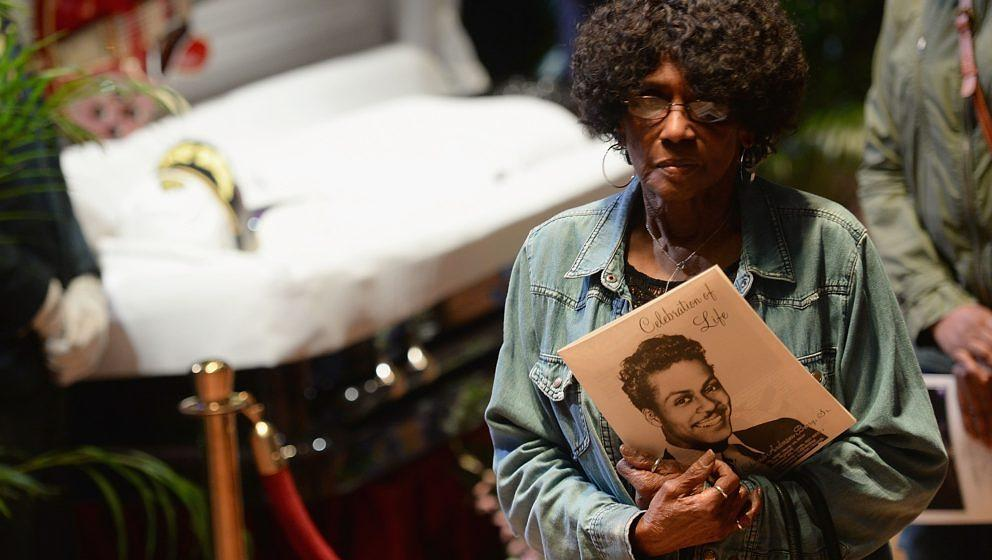 Eine Anhängerin nutzt die Chance, ein persönliches Erinnerungsstück am Sarg von Chuck Berry niederzulegen