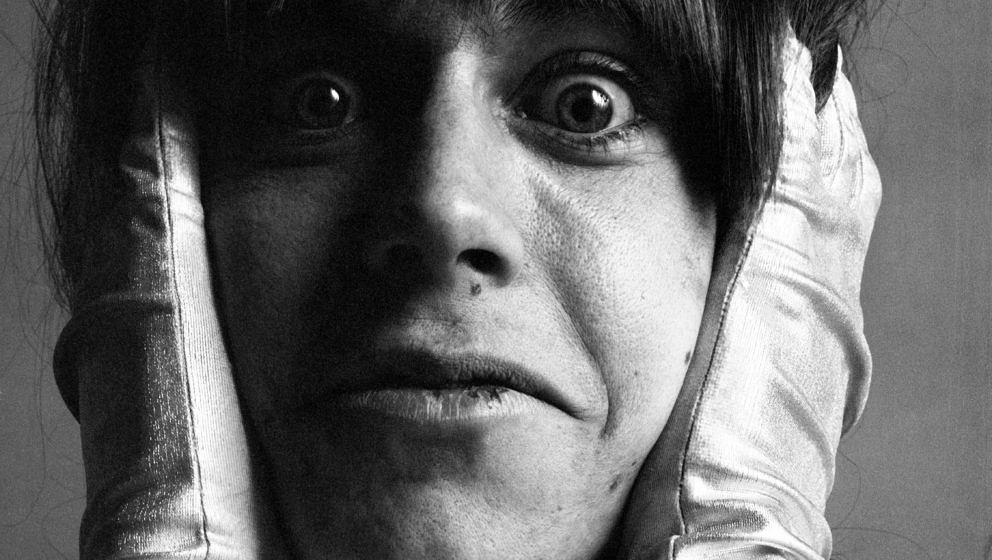 Close-up studio portrait of American rock singer Iggy Pop, of the group the Stooges, as he poses in satin gloves with his han