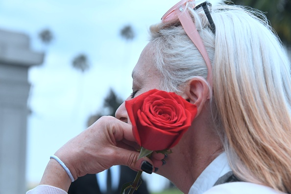 Soundgarden fan Stephanie Sellnau, who came down from San Francisco, holds a rose while grieving the loss of Soundgarden fron
