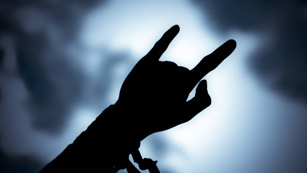 DERBY, UNITED KINGDOM - AUGUST 16:  Metal fan raising arm with devil horn hand gesture in the crowd at Bloodstock Open Air Fe
