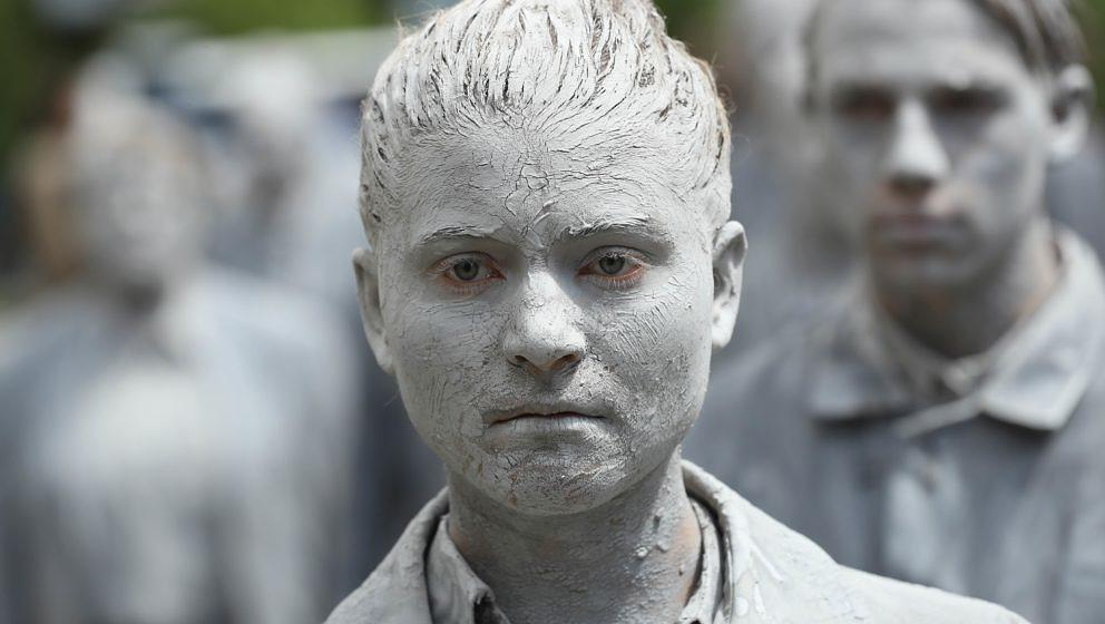HAMBURG, GERMANY - JULY 05:  Performance artists covered in clay to look like zombies walk trance-like through the city cente