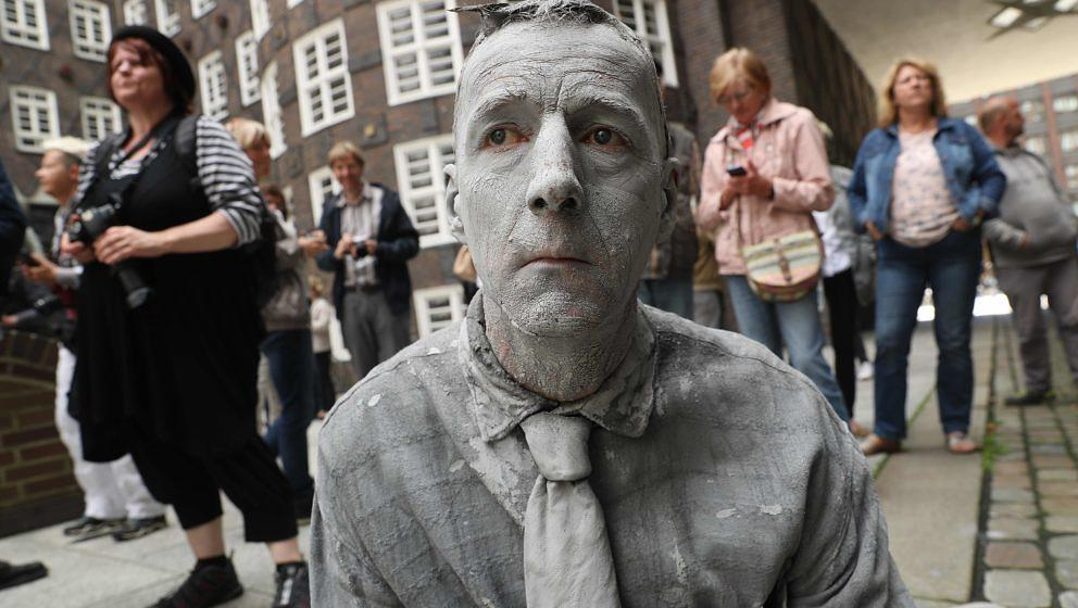 HAMBURG, GERMANY - JULY 05:  A performance artist covered in clay to look like a zombie stumbles trance-like through the city