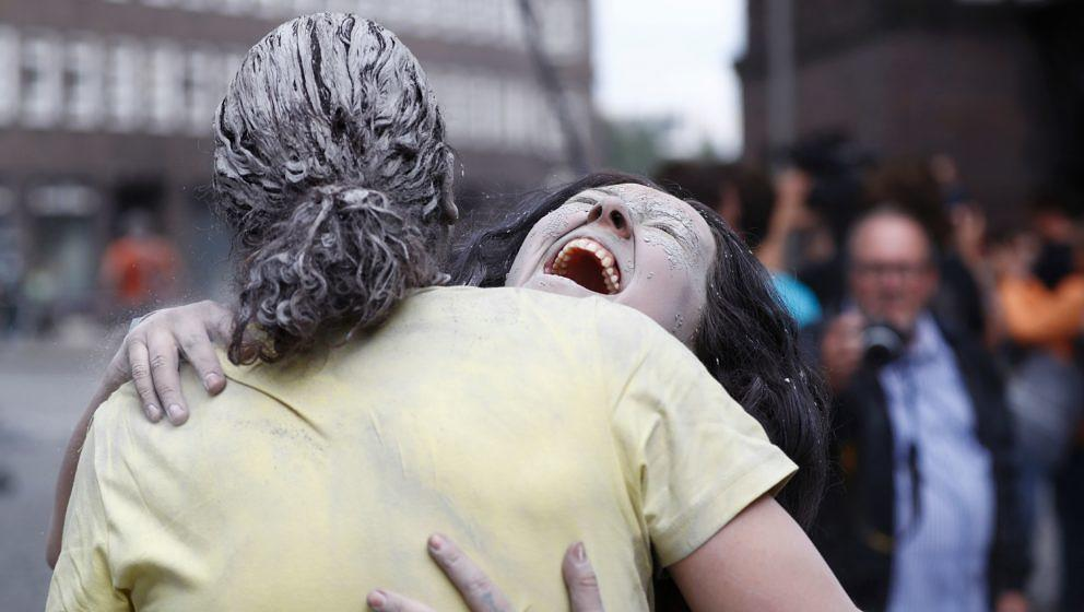 Performers smeared with clay hug during a demonstration during the art action '1000 Gestalten' (1000 figures) on July 5, 2017