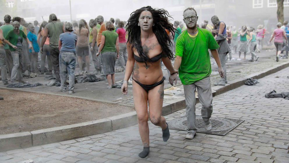 Performers smeared with clay perform during a demonstration during the art action '1000 Gestalten' (1000 figures) on July 5,