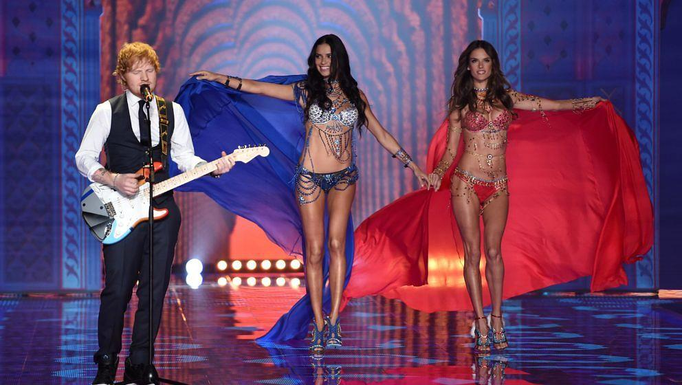 LONDON, ENGLAND - DECEMBER 02:  Singer Ed Sheeran (L) performs on stage as models Adriana Lima (C) and Alessandra Ambrosio wa