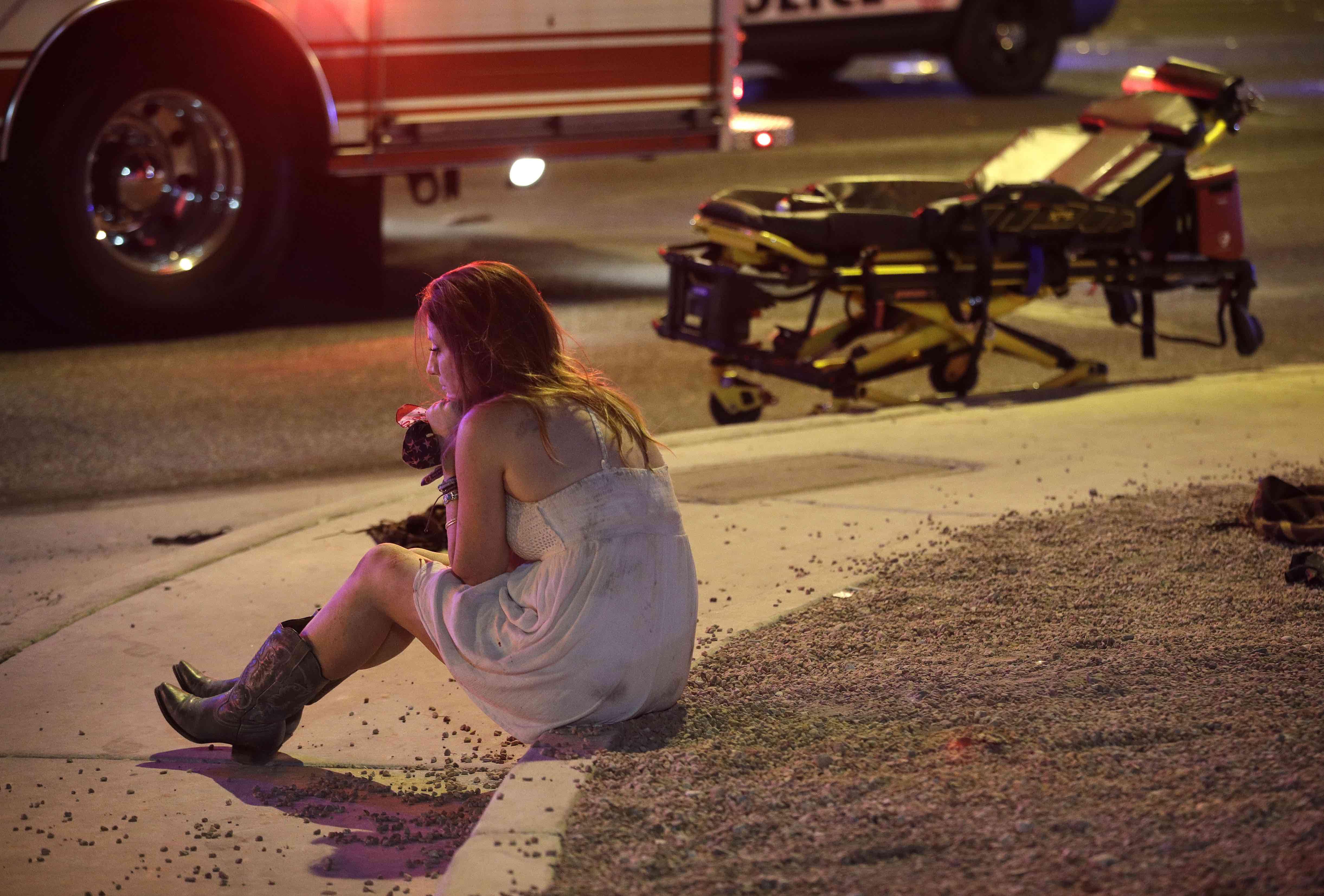 Eine Konzertbesucherin sitzt nach dem Gewalt-Vorfall auf der Straße unweit des Tatorts