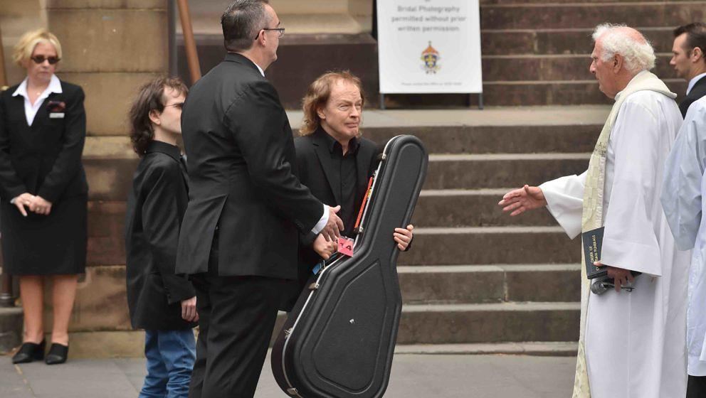 AC/DC guitarist Angus Young (C) carries a guitar case after the funeral service for his brother AC/DC co-founder Malcolm Youn