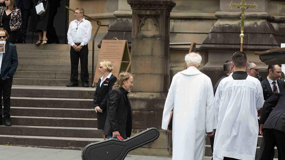 SYDNEY, AUSTRALIA - NOVEMBER 28:  Angus Young, follows his brother's coffin out carrying his guitar at the funeral service fo